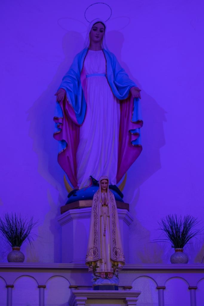 A statue of La Virgin under blue light