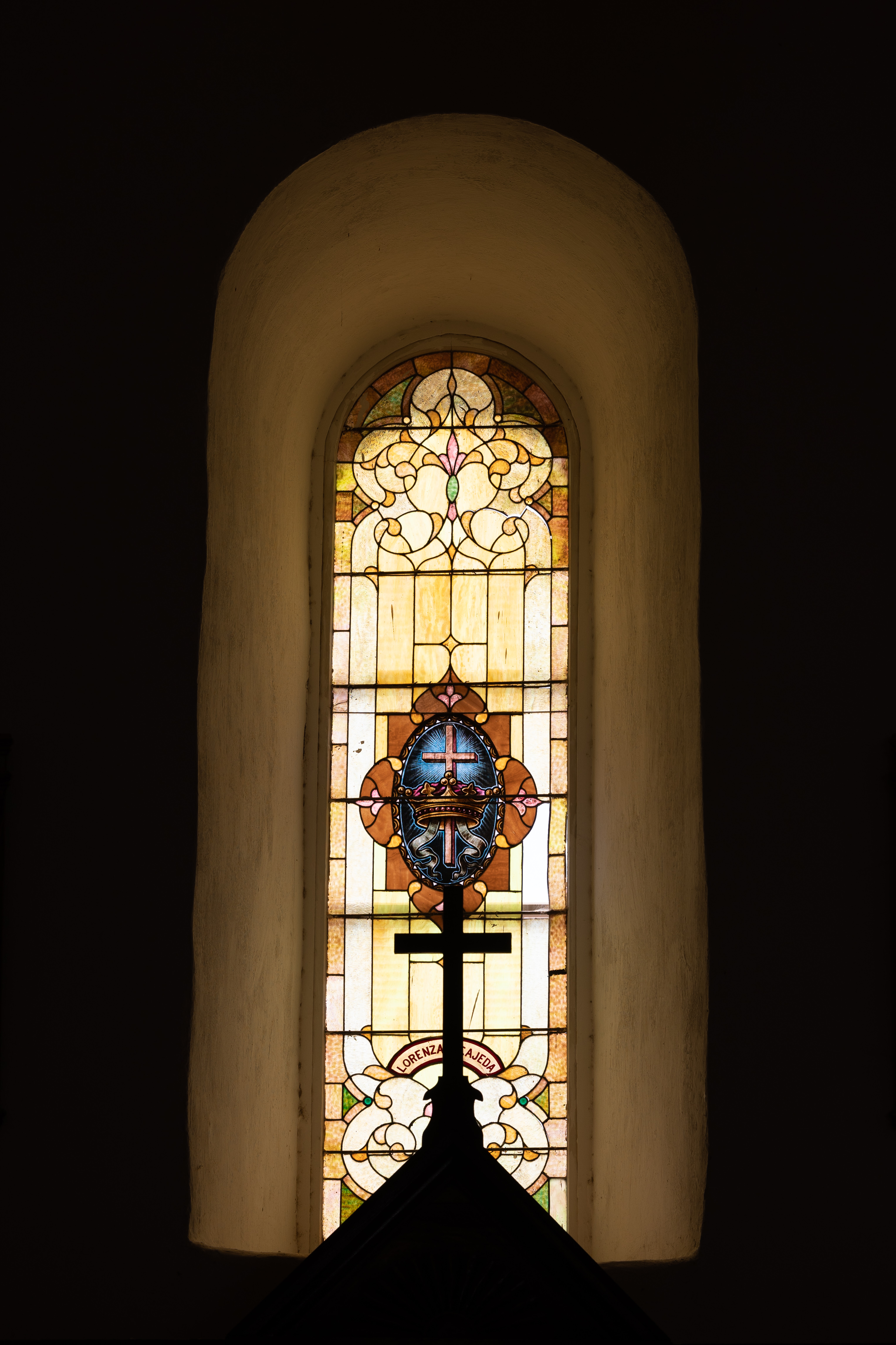 A cross backlight by a tall and thin, pale golden stained glass window featuring a crown and cross.