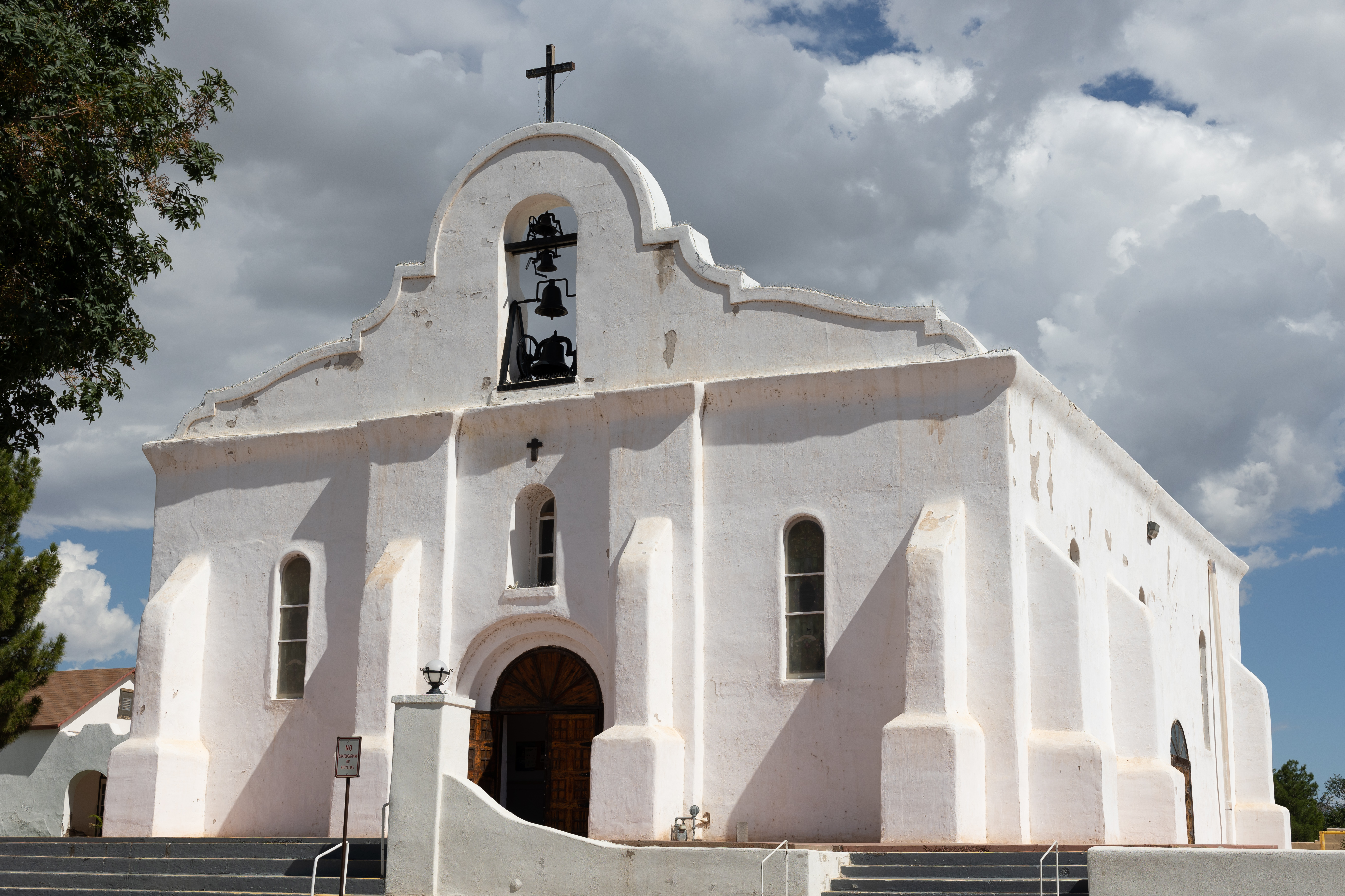 A picture of San Elizario Mission on a partially cloudy day, taken from the Plaza that stands in front of it.
