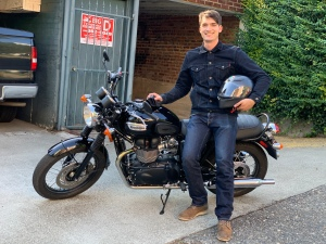 A picture of the author, smiling widely, standing by his newly purchased motorcyle.